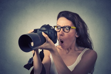 female photographer: Closeup funny looking young woman with digital camera Stock Photo