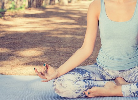 stress free: Cropped image young woman meditating outdoors in spring summer park