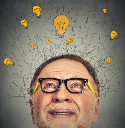above head: Thinking elderly man with question signs and light idea bulb above head looking up on gray wall background Stock Photo