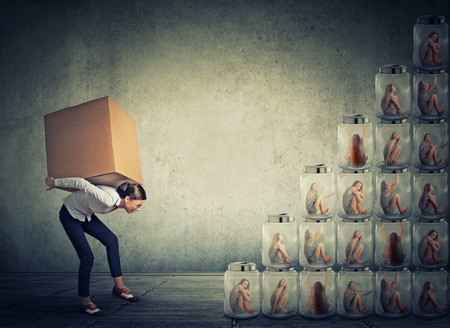 careerist: Young woman with big box on her back climbing up steps made of jars with captive women trapped inside Stock Photo