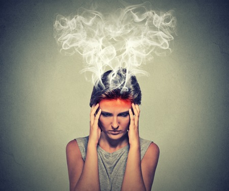 Portrait young stressed woman thinking too hard steam coming out up of head isolated on grey wall background. Face expression emotion perception. Burnout concept
