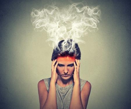 confundido: Retrato joven mujer estresada pensando vapor demasiado duro que sale de la cabeza aislada en el fondo de la pared gris. Cara emoción expresión percepción. Concepto de Burnout Foto de archivo