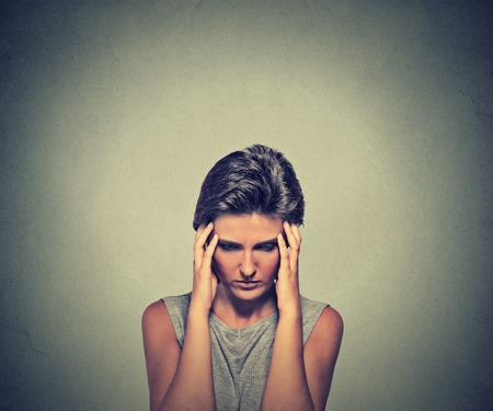 stress test: Stress. Closeup young woman stressed with headache. Female stressed and worried with migraine headache pain Stock Photo