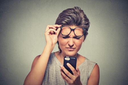 anteojos: Headshot Retrato del primer mujer joven con gafas que tiene problemas para ver teléfono celular tiene problemas de visión. Mensaje de texto Bad. Negativo emoción humana percepción expresión facial. Tecnología Confundir