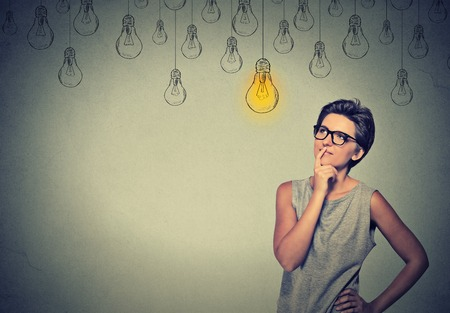 bombillas: Gran idea. Chica inteligente feliz con los vidrios y la solución bombilla encima de la cabeza. Solucionar una idea concepto creativo problema Foto de archivo