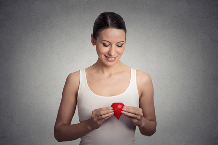 Closeup image young woman holding red drop of blood isolated on gray wall background Stock Photo
