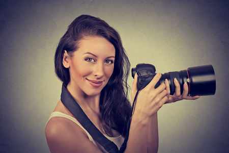 photo shooting: Professional female photographer holding digital camera and smiling