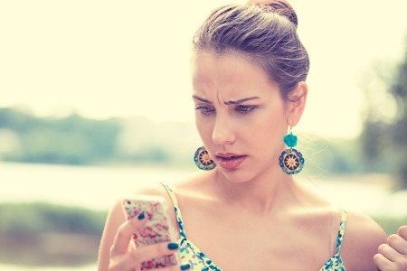 stressed woman: Closeup portrait upset sad skeptical unhappy serious woman talking texting on phone displeased with conversation isolated outdoors park background. Negative human emotion face expression feeling Stock Photo