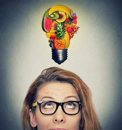 merienda: Comer sano concepto de idea y consejos de dieta. Primer tiro en la cabeza retrato de mujer mirando hacia arriba bombilla hecha de frutas sobre la cabeza sobre fondo gris de la pared.