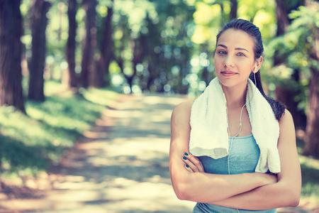 生活方式: 肖像年輕漂亮自信的女人適合用後鍛煉的體育鍛煉在戶外的公園樹木的背景下白毛巾休息。健康的生活方式幸福健康快樂的理念