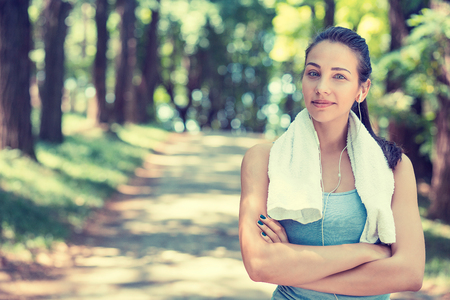 towel: Portrait young attractive confident fit woman with white towel resting after workout sport exercises outdoors on a background of park trees. Healthy lifestyle well being wellness happiness concept Stock Photo