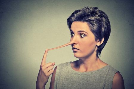 honestidad: Mujer con la nariz larga aislada en el fondo de la pared gris. Concepto mentiroso. Expresiones Humanos cara, emociones, sentimientos. Foto de archivo