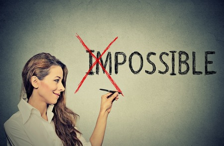 converting: Young happy woman converting the word impossible to possible. Positive thinking and success concept