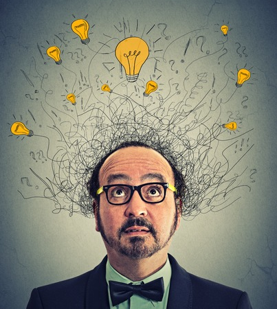 Thinking man with question signs and light idea bulbs above head looking up isolated on gray wall background