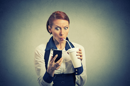 sms: Closeup portrait surprised business woman reading breaking news on smart phone drinking soda coffee isolated on grey wall background. Human face expression, corporate executive emotions Stock Photo