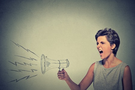 propaganda: Portrait angry young woman holding screaming in megaphone isolated grey wall background. Negative face expression emotion feelings. Propaganda, breaking news, power, social media communication concept Stock Photo