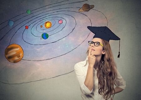 student life: Closeup portrait young woman student dreaming, thinking about future, life on other planets, isolated on gray space background with stars planets