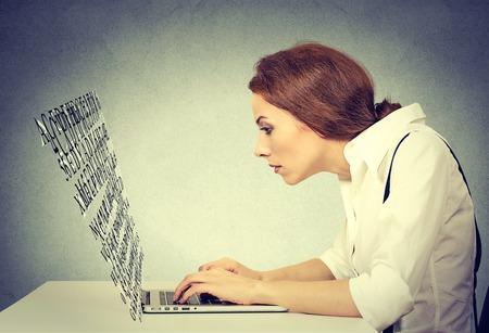 teclado de computadora: Mujer escribiendo en su computadora portátil con la pantalla hecha de letras del alfabeto volando Foto de archivo