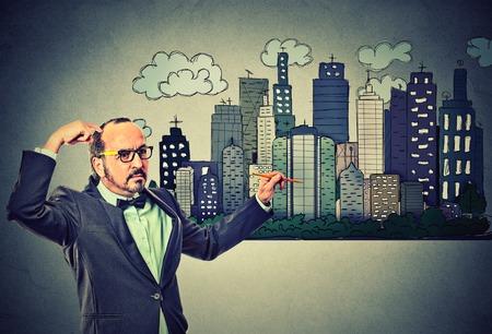 bienes raices: Hombre dibujando horizonte de la ciudad en el fondo gris de la pared. Desarrollo inmobiliario, la economía de mercado la casa, la inversión concepto de oportunidad