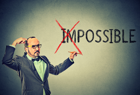 converting: Middle aged thoughtful man with glasses converting the word impossible to possible. Positive thinking and success concept
