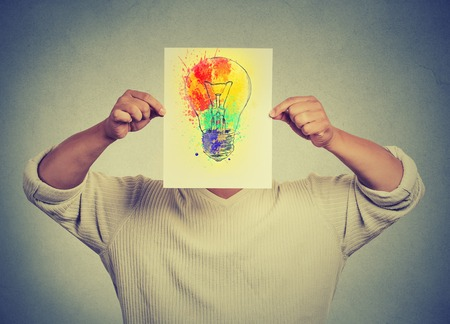 thinking: Man having brilliant idea colorful lightbulb covering face isolated grey wall background. Free thinking, new approach, alternative technology. Creativity, imagination, dynamism, intelligence concept Stock Photo