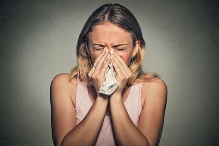 nariz: Brunette estornudar en un pañuelo de papel que sopla su nariz que moquea
