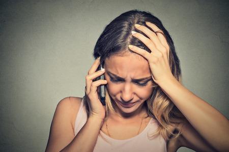 problemas familiares: Retrato infeliz mujer joven hablando por tel�fono m�vil mirando hacia abajo. Expresi�n del rostro humano, la emoci�n, la reacci�n de malas noticias Foto de archivo