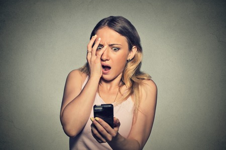 breakup: Closeup portrait anxious scared young girl looking at phone seeing bad news photos message with disgusting emotion on her face isolated on gray wall background. Human reaction, expression
