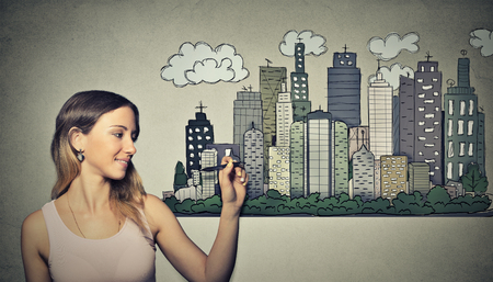 opportunity: Woman drawing city skyline on grey wall background. Real estate development, house market economy, investment opportunity