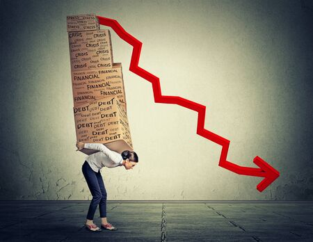 global crisis: Young woman carrying heavy boxes full of financial debt walking along gray wall background Stock Photo