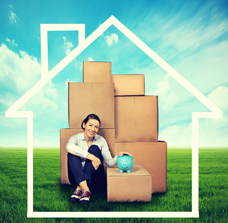 sitting on the ground: young woman sitting on the ground with many boxes and piggy bank