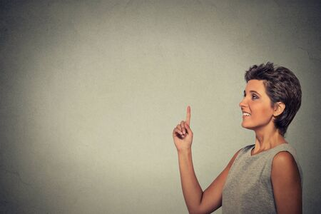copyspace: woman pointing at copyspace isolated on gray wall background