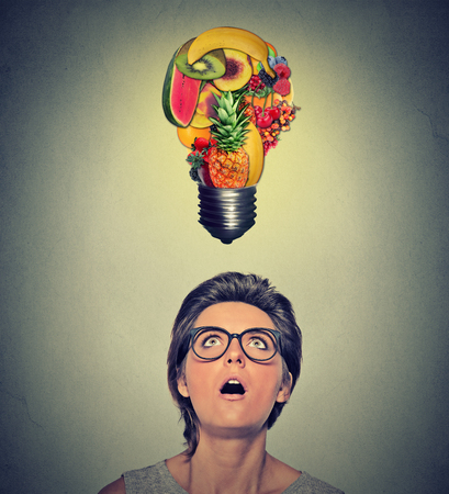 woman looking up: Eating healthy idea and diet tips concept. Closeup portrait headshot surprised woman looking up light bulb made of fruits above head on gray wall background.
