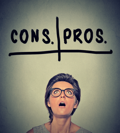 decisions: pros and cons, for and against argument concept. Young business woman with glasses looking up deciding isolated on gray wall background. Face expression, emotion, feeling, perception, vision, decision