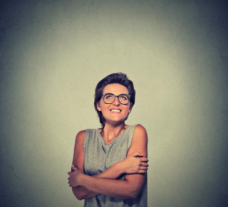 self conceit: Closeup portrait smiling woman with glasses holding hugging herself isolated grey wall background. Positive human emotion facial expression feeling, reaction, attitude. Love yourself concept