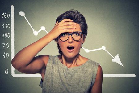 pobre: Sorprendida mujer joven emocional desesperada con la carta de los mercados financieros gráfico que va abajo en la pared de fondo gris de la oficina. expresión de la cara reacción humana