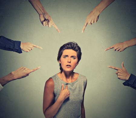 pointing at: Concept of accusation guilty person girl. Upset angry looking woman asking me? many fingers pointing at her isolated on grey office wall background. Human face expression emotion feeling reaction Stock Photo
