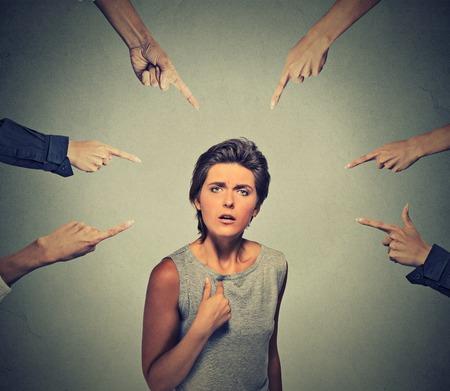 Concept van beschuldiging schuldige meisje. Verstoor boze uitziende vrouw vraagt me? vele vingers wijzen op haar geïsoleerd op kantoor grijze muur achtergrond. Menselijk gezicht meningsuiting emotie gevoel reactie Stockfoto