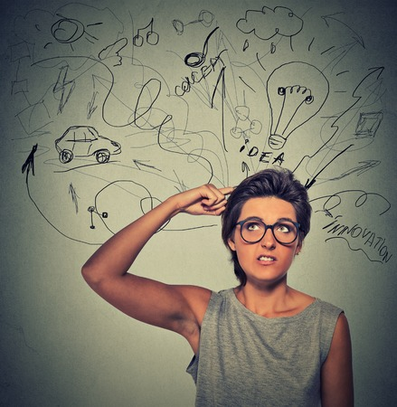 Closeup portrait wondering young woman has many ideas isolated on gray wall background