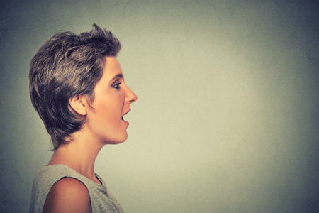 sentence: Closeup side view profile portrait woman talking with sound coming out of her open mouth isolated grey wall background. Human face expression emotions. Communication, information, intelligence concept