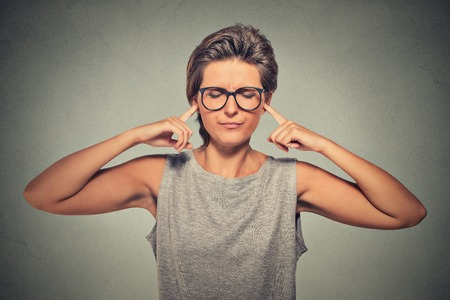 Woman plugging ears with fingers doesn't want to listen eyes closed ignoring stressful unpleasant situation conflict Stock Photo