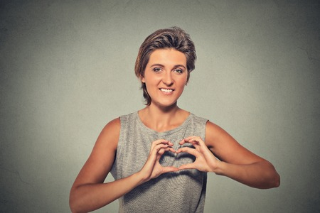 feeling happy: Closeup portrait smiling cheerful happy young woman making heart sign with hands isolated on gray wall background. Positive human emotion expression feeling life perception attitude body language