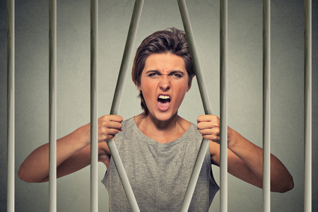 femme triste: Souligné désespérés femme flexion colère barreaux de sa cellule de la prison sur le gris mur arrière-plan. Limitations de la vie, le droit abus conséquences d'évasion fiscale d'infraction concept. Visage expression émotion