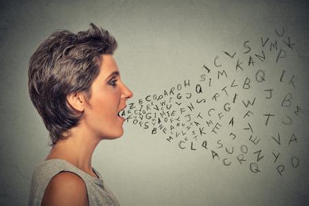 알파벳 문자가 그녀의 입에서 나오는 얘기 측면 프로필 여자. 통신, 정보, 정보의 개념 스톡 콘텐츠