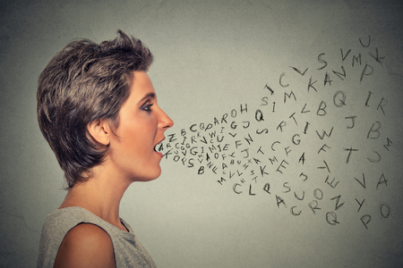 Side profile woman talking with alphabet letters coming out of her mouth. Communication, information, intelligence concept