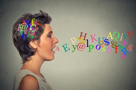 Side view portrait woman talking with alphabet letters in her head and coming out of her open mouth isolated grey wall background. Human face expressions, emotions. Communication, intelligence concept