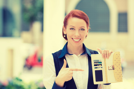 point: Portrait of young smiling business woman holding pointing at many credit cards in her wallet Stock Photo