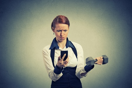 user: Portrait angry young business woman reading news e-mail on mobile phone lifting dumbbell isolated on gray office wall  Stock Photo