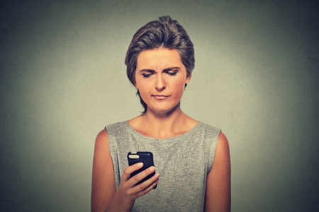 family problems: Closeup portrait upset sad skeptical unhappy serious woman talking texting on mobile phone displeased with conversation isolated on gray background. Negative human emotion face expression feeling Stock Photo