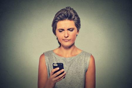 problemas familiares: Retrato del primer trastorno triste escéptico mujer seria infeliz hablar los mensajes de texto en el teléfono móvil descontento con la conversación sobre fondo gris. Emoción humana sensación de expresión de la cara negativa